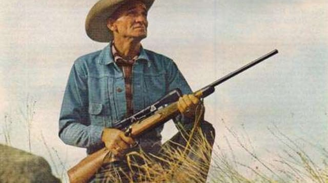 An artist's depiction of what it looks like to wear a jean jacket, cowboy hat and carry a Remington 700 hunting rifle through the grass.