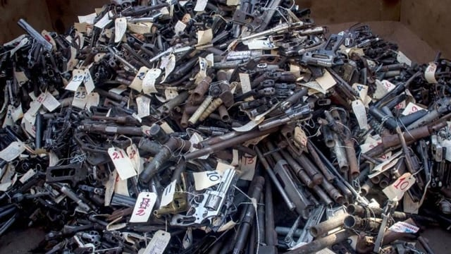 hundreds of handguns and revolvers in a pile on top of eachother