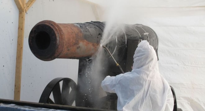 Conservators use super heated water at extremely high pressure to remove layers of paint on an 1830 seacoast artillery piece at Fort Moultrie on Sullivans Island, S.C., on Friday, Dec. 13, 2013. Fort Sumter has 11 similar Parrot rifles that need similar work (Photo: AP/Bruce Smith)