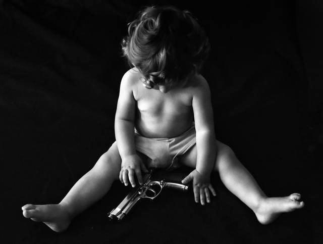 baby sitting next to handgun