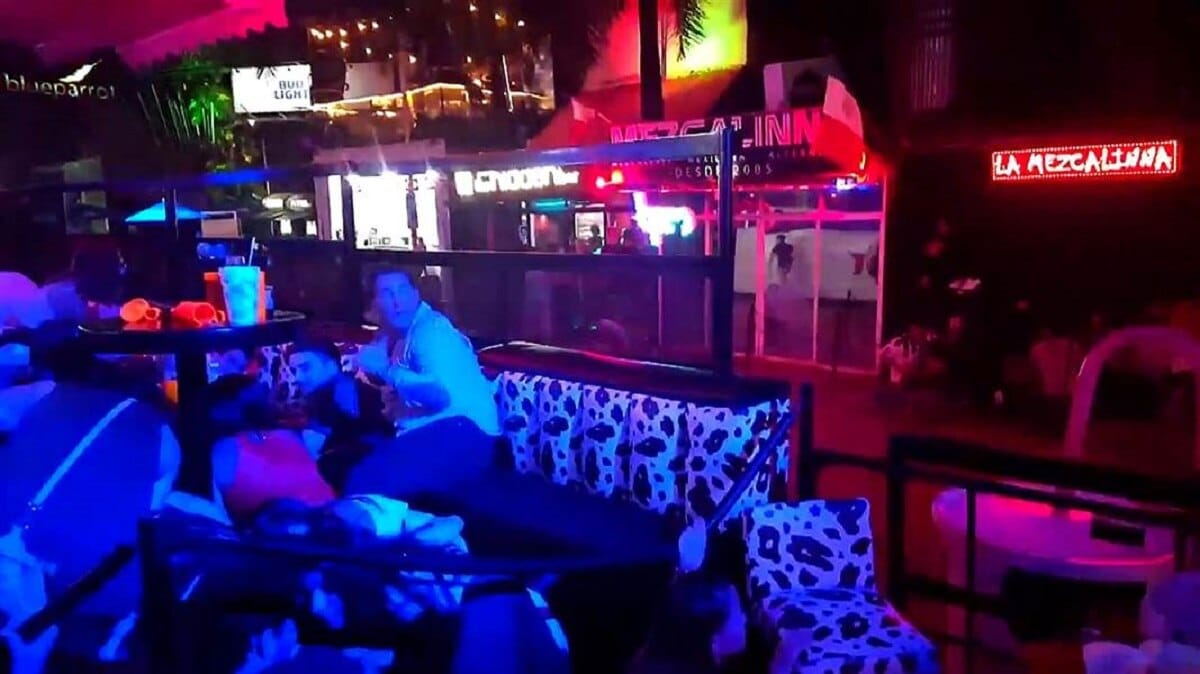 People hide beneath tables during shooting at a Playa del Carmen nightclub in Mexico (Photo: NBC News)