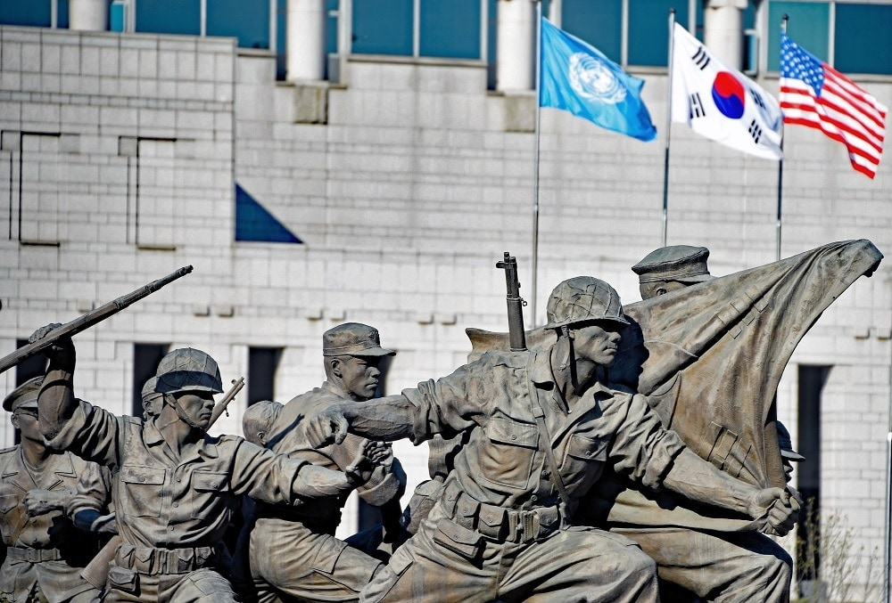 The United Nations, Republic of Korea and U.S. flags fly in the background of a statue depicting Soldiers armed with M1 rifles fending off a North Korean attack during the Korean War outside the War Memorial of Korea in Seoul. (Photo: U.S. Army)