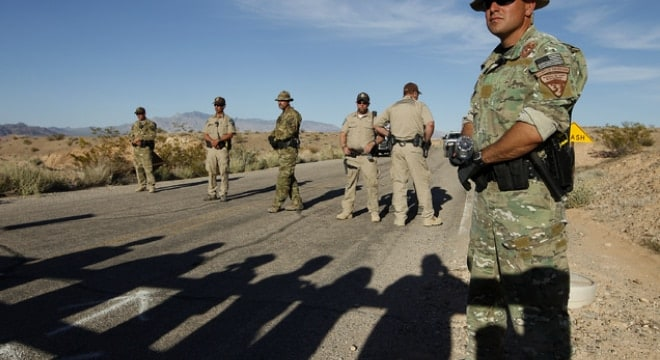 BLM law enforcement officers block the Overton Beach Road at the Lake Mead National Recreation Area near Overton, Nevada on April 10, 2014. The shadows of people protesting the roundup of cattle owned by Cliven Bundy are seen in the foreground. (Photo: John Locher/Las Vegas Review-Journal)
