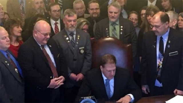 N.H. Gov. Chris Sununu signs the constitutional carry bill into law (Photo: NRA-ILA)