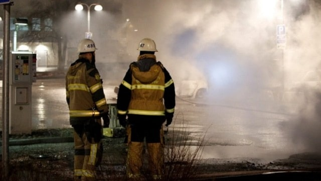 Firefighters attend to cars smoking after being set on fire in a Stockholm suburb (Photo: Reuters)