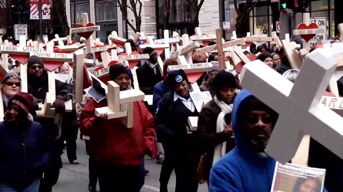 People carry crosses with names of gun violence victims during a Dec. 31 march in downtown Chicago (Photo: Vice News)