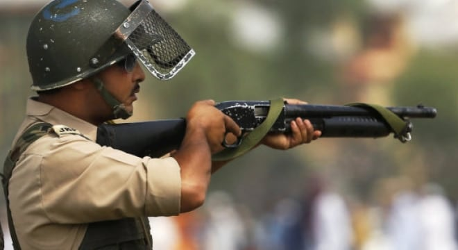 An Indian policeman aim his pellet gun at protesters during a protest in Srinagar, India (Photo and caption: AP)