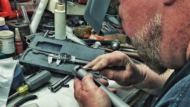 A Colt assembler tinkering with the slide to a 1911 pistol. (Photo: Colt/Facebook)