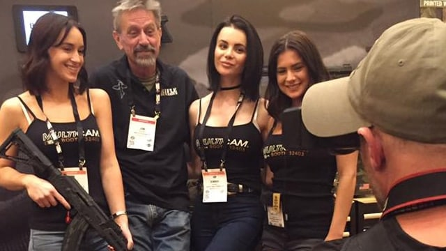 Jim Fuller, owner of Rifle Dynamics, posing with booth babes at SHOT Show 2017. (Photo: Daniel Terrill/Guns.com)