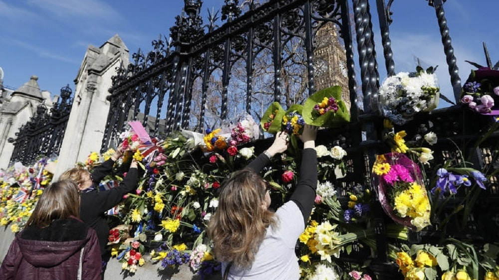 People pay tribute to the victims of the Westminster attack by placing flowers outside Parliament (Photo: AP)