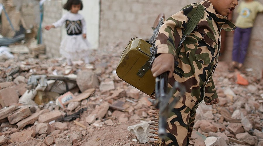 Armed boy walks through rubble in war-torn Yemen (Photo: Reuters)