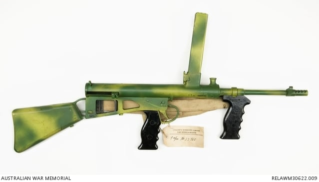 Production Owen Mk 1 painted in green and yellow camouflage for use in jungle fighting. The pistol grips are black plastic and the butt is wood.