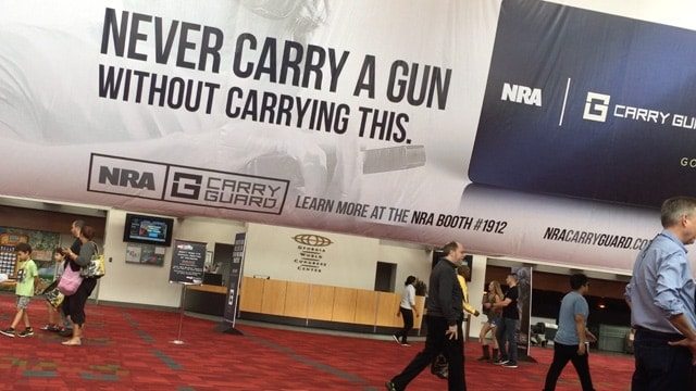 The NRA greeted guests with a sign promoting its new self-defense insurance during the organization's annual conference in Atlanta from April 27-30, 2017. <em>(Photo: Daniel Terrill/Guns.com)</em>