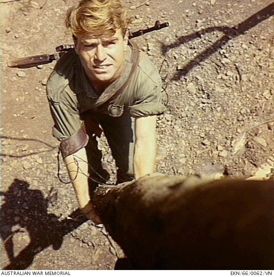 """And in Vietnam. AWM caption: """"Nui Dat, South Vietnam. 1966. A Signal Corps linesman with a 9mm Owen Machine Carbine (Owen Gun) on his back, climbing a rubber tree at 1st Australian Task Force (1ATF) Base."""""""