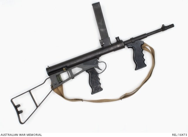 Owen Mk 1/43 Sub-machine Gun complete with canvas sling mounted on the left-hand side. The butt is the skeleton frame type with a clip for an oil bottle-- similar to the one found on the U.S. M1A1 Carbine.