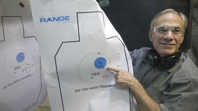 Texas Gov. Greg Abbott holds up his target sheet to reporters after firing off a couple rounds at an Austin shooting range. (Photo: Austin American-Statesman)
