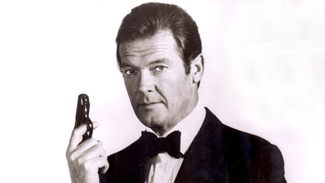 Roger Moore poses as James Bond with his Walther PPK pistol. (Photo: Moviestore/Rex Shutterstock)