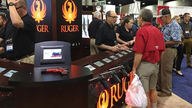 A man with a bag of stuff wanders through the Ruger booth at the NRA annual conference. (Photo: Ruger)