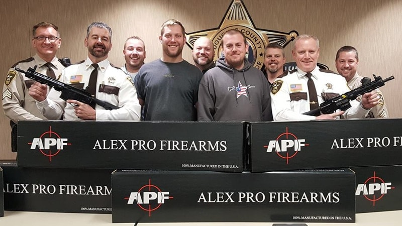 Alex Pro Firearms employees Garrett Streitz, center left, and Jason Leigh pose after delivering rifles to the Douglas County Sheriff's Department in Minnesota in January. (Photo: APF)