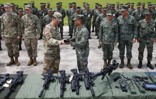 Philippine Marine Maj.Gen. Emmanuel Salamat, receives a new M4 rifle with attached M203 grenade launcher from U.S. Army Col. Ernest Lee during turnover of weapons and other equipment on June 5. (Photo: Bullit Marquez/AP)