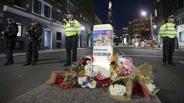 Police officers on duty stand next to floral tributes on Southwark Street in London, Sunday, June 4, 2017, near the scene of Saturday's attack. A series of attacks described as terrorism killed several people and injured dozens on Saturday. (Yui Mok/PA via AP) - See more at: https://880thebiz.com/news/world/london-police-arrest-more-suspects-in-bridge-attack#sthash.hUNABFuS.dpuf