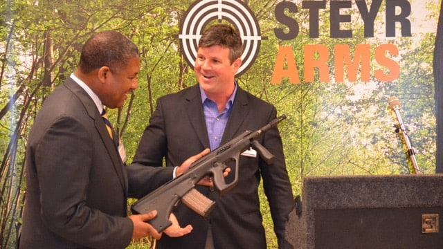 Bessemer Mayor Kenneth Gulley, left, receives the first AUG rifle Steyr Arms assembled in Bessemer from Scott O'Brien, Steyr's president in April 2014. (Photo: Michael Tomberlin/AL.com)