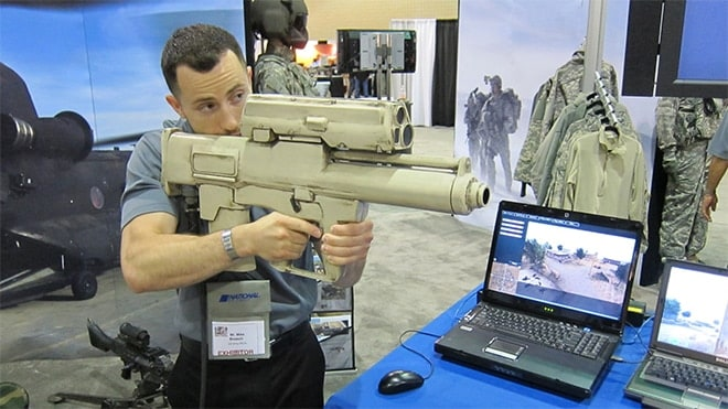 "A U.S. Army acquisitions representative looks through the scope of the XM25 shoulder-fired 25mm airburst grenade system, dubbed ""the Punisher."" (Photo: Defense Review)"
