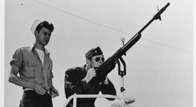 """Lt. JG Rothschild on the skeet range at NAS Saint Louis, Missouri, April 1944. The """"machine gun"""" is a Remington Model 11 on a Mk. 1 Mod. 0 mount. They are using Peters """"Victor"""" brand paper hulled shells. (Photo: U.S. Navy)"""