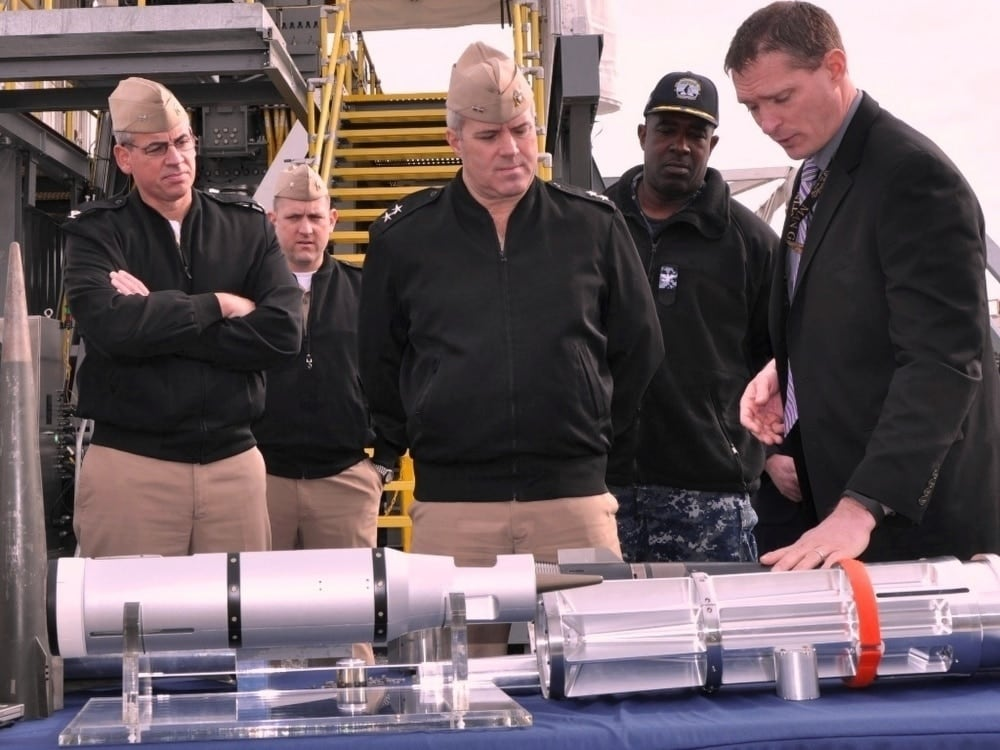 The electromagnetic railgun projectile is a 35-pound dart incased in a discarding sabot shown below being exhibited by Adam Jones, a Naval Surface Warfare Center Dahlgren Division engineer, to Rear Adm. Ronald Boxall, director of Surface Warfare (OPNAV N96), on , Jan 19, 2017 (Photo: U.S. Navy)