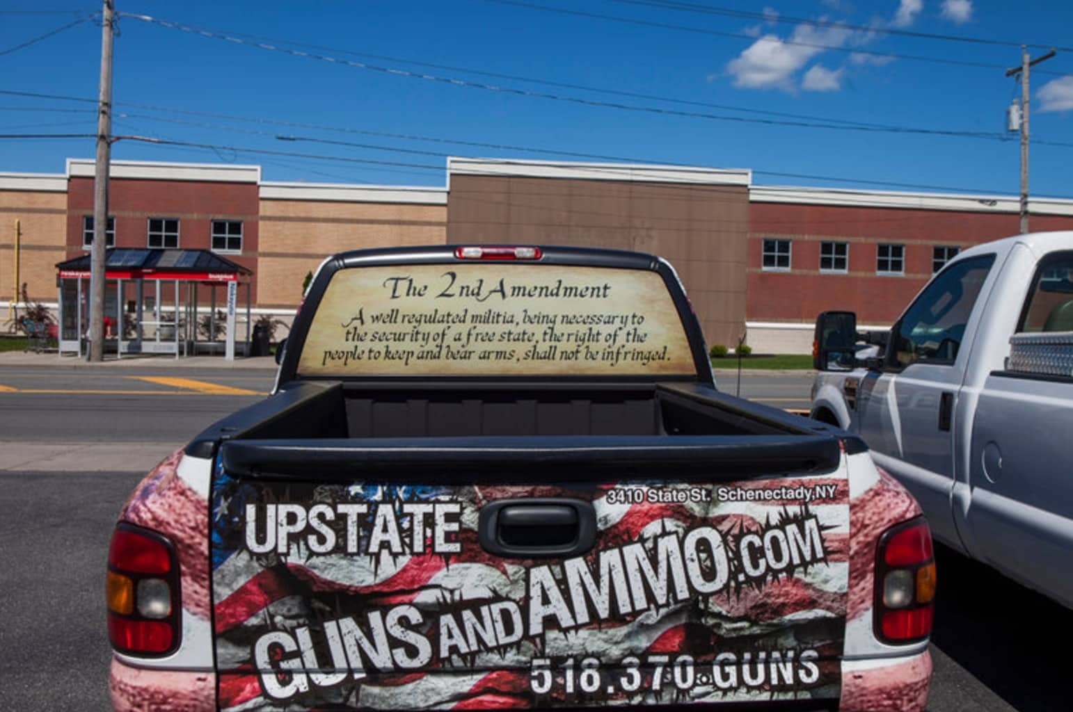 A truck is wrapped in graphics reading Upstate Guns and Ammo, the store Henry Bello legally purchased the AM-15 rifle he used to allegedly kill a clinician and himself after wounding six others at a Bronx hospital last week. (Photo: New York Times)