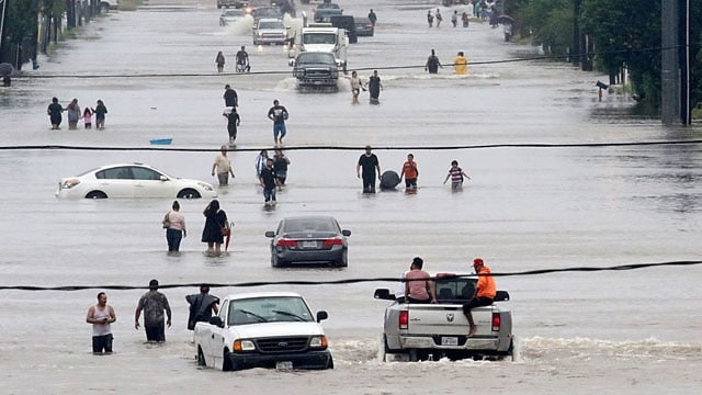 People waded through floodwaters in Houston on Sunday. (Photo: Thomas B. Shea/Agence France-Presse — Getty Images)