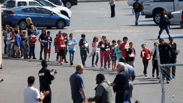 Students who were evacuated after a shooting at North Park Elementary School walk past well-wishers to be reunited with their waiting parents at a high school in San Bernardino, California, U.S. April 10, 2017. (Photo: Mario Anzuoni/ Reuters)