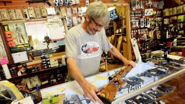 Gene Mock, co-owner of Ron's Guns, helps a customer in Bossier City, Louisiana. (Photo: Henrietta Wildsmith/The Times)