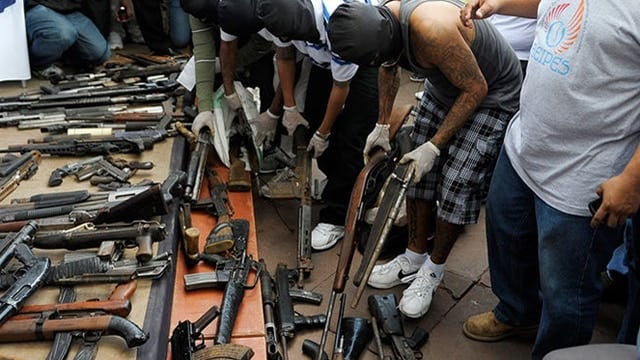 Masked gang members hand over weapons during a symbolic act for peace at Gerardo Barrios Square in San Salvador, El Salvador, on July 12, 2012. (Photo:Jose Cabezas/AFP/Getty Images)