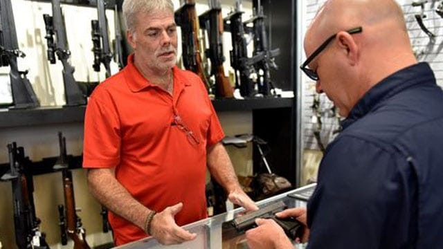 In this file photo, Randy Crocker , left, with USA Pawn, shows Hal Finch of Madison a pistol in the store on I-55 at McDowell Road in Jackson. Mississippi has removed the 7 percent state sales tax on guns, ammunition, archery equipment and some hunting supplies for the first weekend each September. (File photo/The Clarion-Ledger)