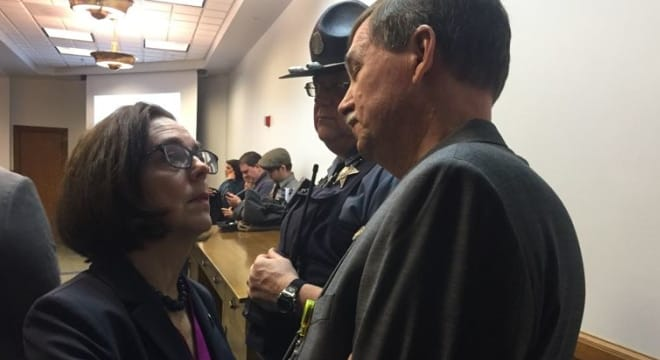 Gov. Kate Brown speaks to Sen. Brian Boquist, R-Dallas, before an April 2017 hearing on the Extreme Risk Protection Order bill at the Oregon Capitol in Salem. Boquist sponsored the legislation after the suicide of his son. (Photo: Paris Achen/Capital Bureau)