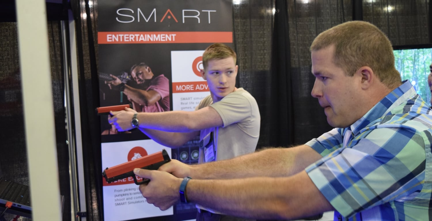 Two men who are quite possibly relatives shoot at one of the many simulators on the show floor. (Photo: Daniel Terrill/Guns.com)
