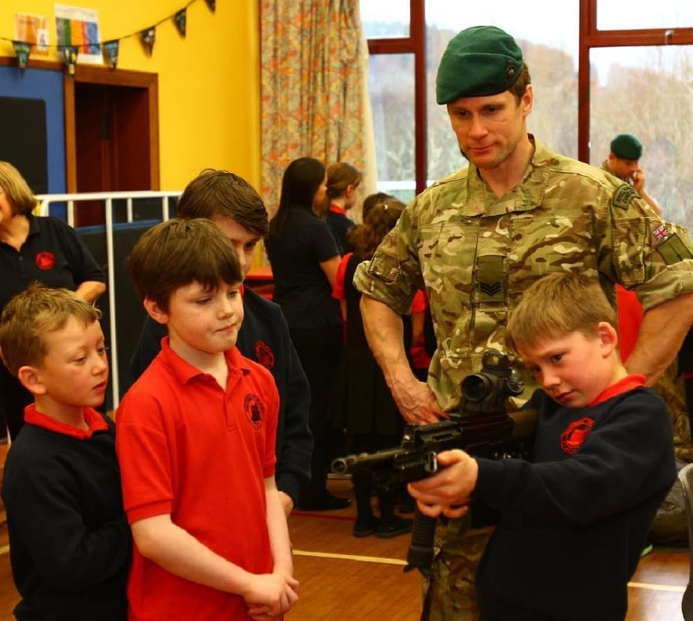 A Royal Marine shows his firearm to students during a previous visit. (Photo: The Scottish Sun/Kevin McGlynn)