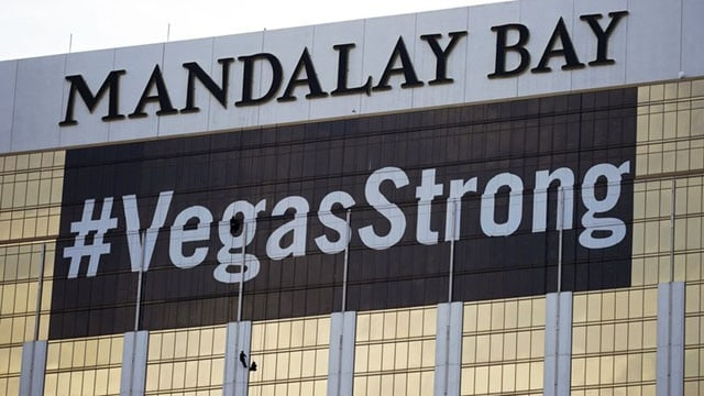 An Oct.16, 2017 file photo featuring workers installing a #VegasStrong banner on the Mandalay Bay hotel and casino. (Photo: John Locher/AP Photo)