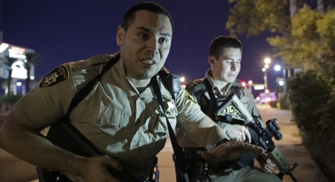 In this Oct. 1 file photo, police officers advise people to take cover near the scene of a shooting near the Mandalay Bay resort and casino on the Las Vegas Strip in Las Vegas. (Photo: John Locher/AP)