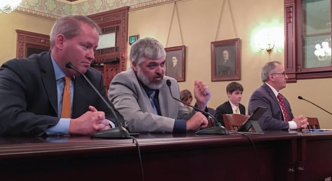 NRA lobbyist Todd Vandermyde, second from left, talks about bump stocks at a hearing of the Illinois House Judiciary Criminal Law Committee. Illinois State Rifle Association lobbyist Ed Sullivan is at left; Rep. Marty Moylan, D-Des Plaines, is at right. (Photo: Brian Mackey/NPR Illinois)