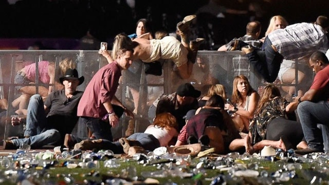 People scramble for shelter at the Route 91 Harvest country music festival, Oct. 1, 2017, in Las Vegas. (Photo: David Becker/Getty Images)