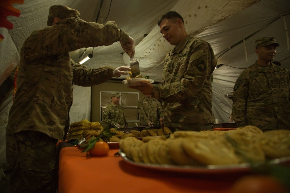 """""""U.S. Army leadership assigned to 2nd Brigade Combat Team, 101st Airborne Division serve their Soldiers a Thanksgiving meal at Tactical Assembly Area Shaquli in support of Operation Inherent Resolve, Iraq, Nov. 24, 2016"""" (Photo: Department of Defense)"""