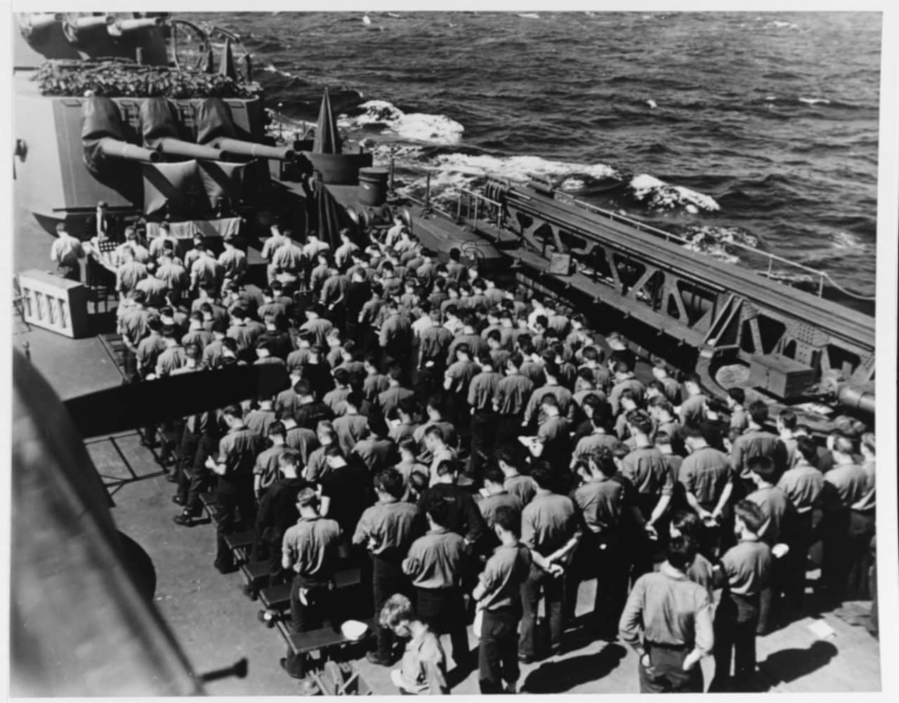 """USS Santa Fe (CL-60) crewmembers attend Thanksgiving Day services on the ship's after deck under a 6"""" gun turret, probably during the Gilberts campaign in November 1943 (Photo: National Archives)"""