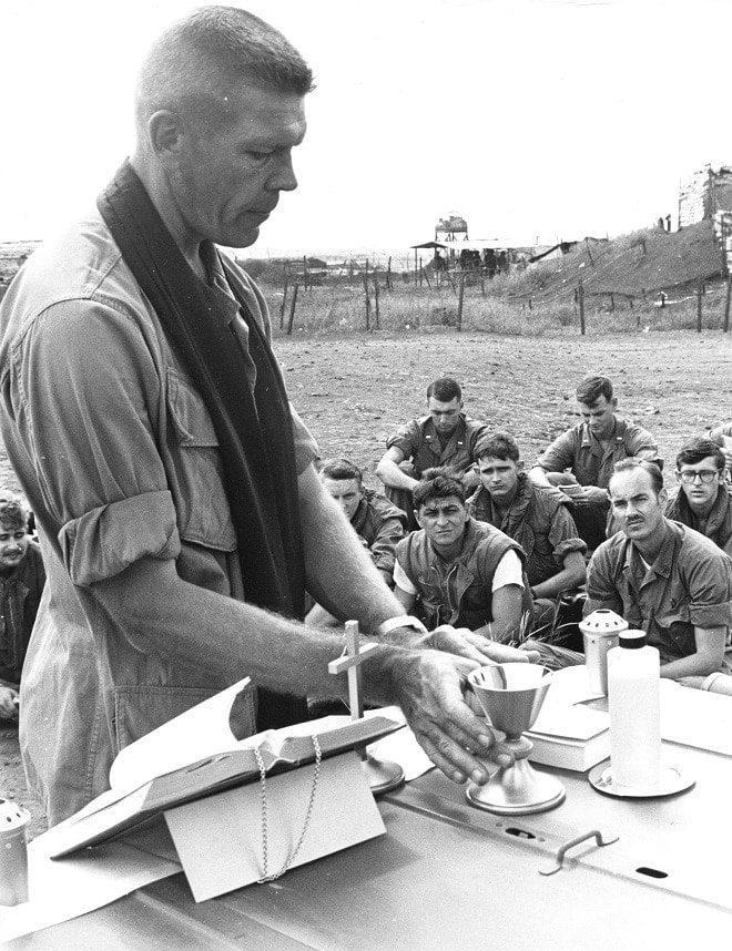 """""""The hood of a jeep serves as a makeshift altar as Commander Martin J. Doermann (North Kingston, R.I.) Twelfth Marine Regimental Chaplain, holds Thanksgiving Day services at Gio Linh, south of the Demilitarized Zone. The chaplain was one of a score of 3d Marine Division chaplains that visited Marine units in the field as Marines observed Thanksgiving Day in Vietnam."""" November 1968 (Photo: USMC)"""