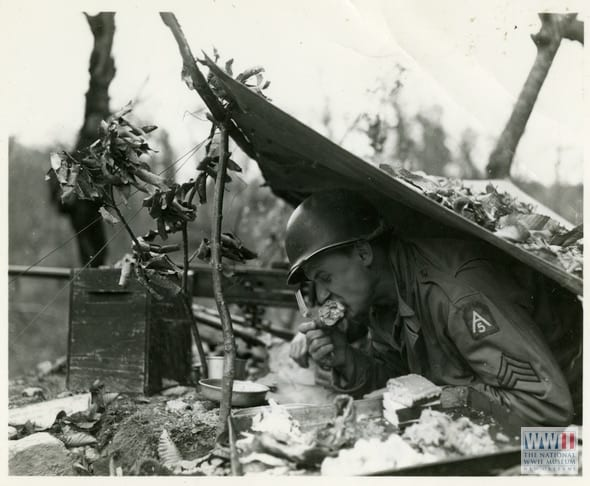 """Photograph. '22 Nov 44. 5/MM-44-30207. Fifth Army, San Marcello Pistoiese Area, Italy. Thanksgiving chow went as far forward as there were troops. Sgt. Frank Shiborski, 107 AAA Group, from 5007 Central Ave, Detroit, Mich.[Michigan] A 50 Cal. Machine gunner, takes time out from looking for Germans to do a little special duty on a 'drum stick.' Photo by Edwards. 3131 Signal Service Co.' San Marcello Pistoiese Area, Italy. 22 November 1944"" (Photo: National WWII Museum)"