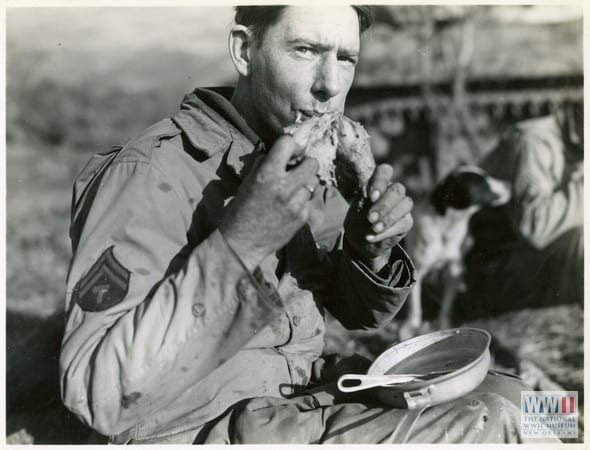 """Photograph. '17 Nov 44. 5/MM-44-6887. Fifth Army, San Benedetto Area, Italy. T/5 Wm. [William] Fleming, Austin, Minn. [Minnesota], eating turkey leg. Photo by Schmidt. 3131 Signal Service Co.' San Benedetto Area, Italy. 17 November 1944"" (Photo: National WWII Museum)"