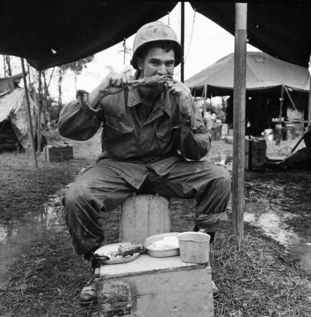 """Marine Lance Corporal Douglas E. Parker (Portland, Oregon), of F Company, 3rd Battalion, 9th Marines, tears into a hefty drumstick while enjoying a real home-style Thanksgiving dinner. Marines throughout Vietnam were served a full course turkey dinner on Thanksgiving Day"", November 25, 1965 (Photo: National Archives)"