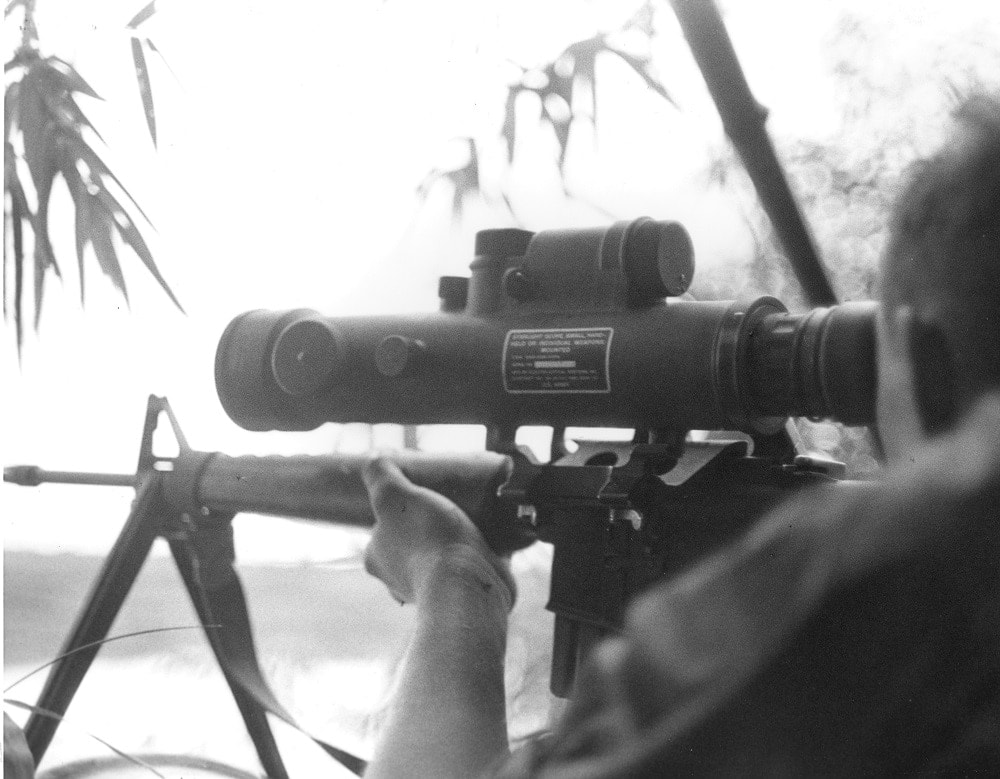 A Marine sniper with an early M16 equipped with a Starlite scope is silhouetted while taking aim at an enemy target at dusk during Operation Shelby, 15 miles south of Da Nang. September 1 1967
