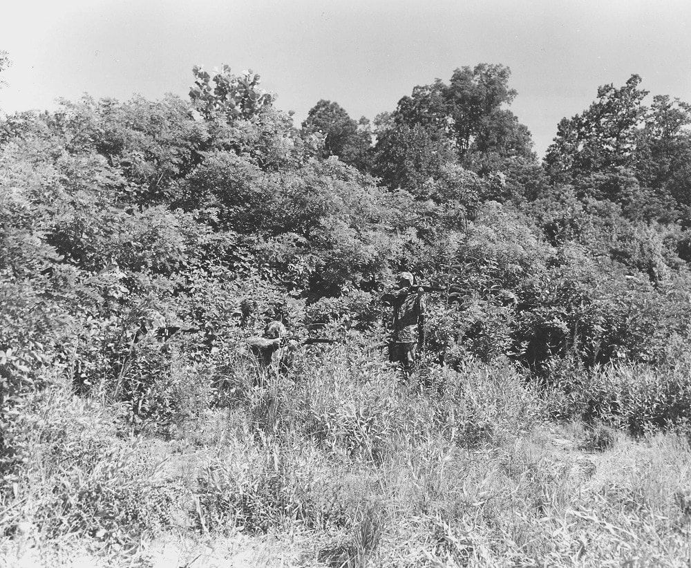 """Attired in sniper outfits and armed with M1903s, three students of the Marine Corps camouflage School at Quantico, Va., hide in the grass and trees. August 13 1942"" (Photo/caption: U.S. Marine Corps History Division)"